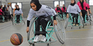 girl in wheelchair playing adapted basketball wearing hijab recreation therapy