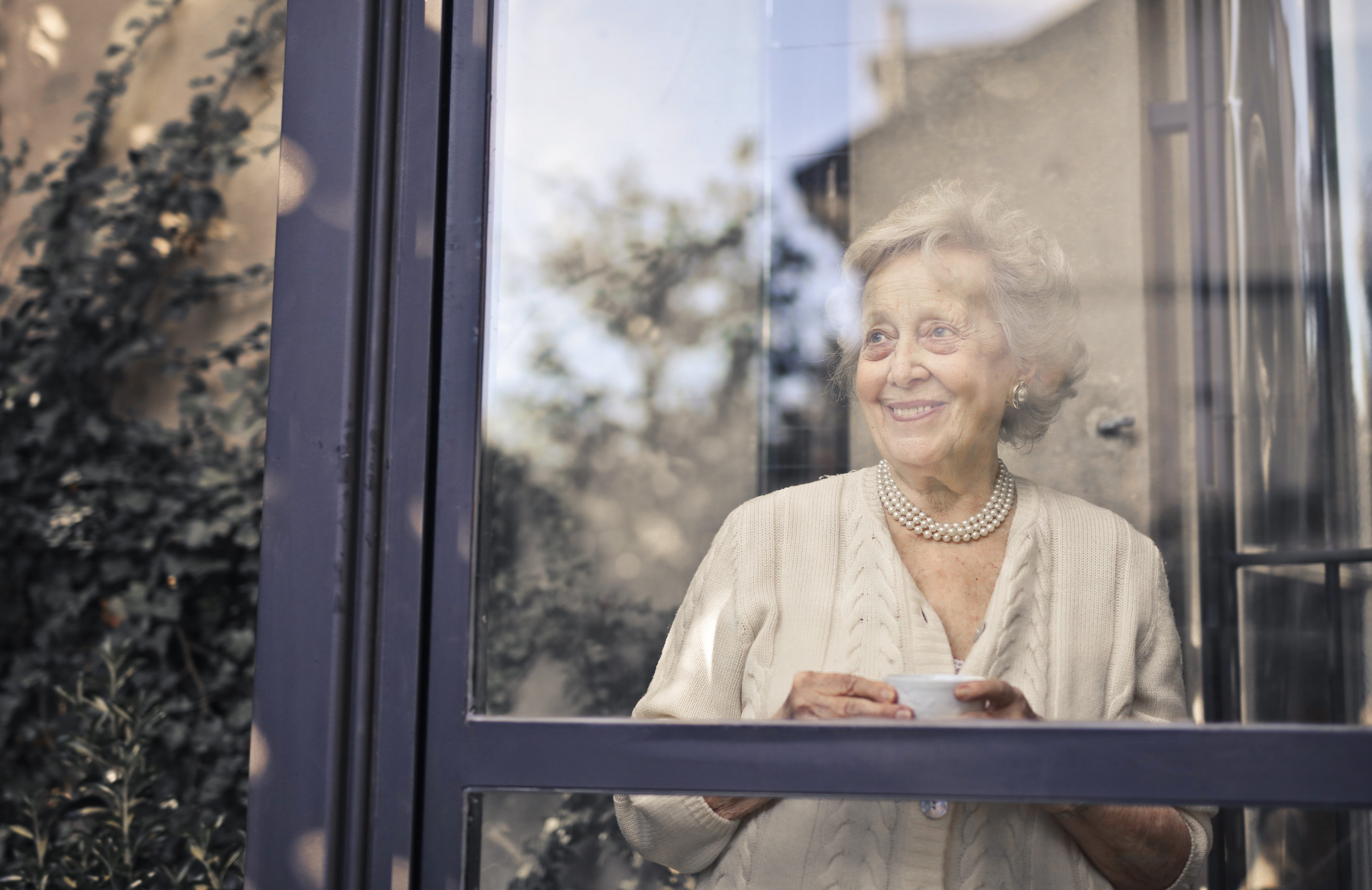 Socially isolated senior during COVID-19 pandemic looking out her window while holding a mug of tea