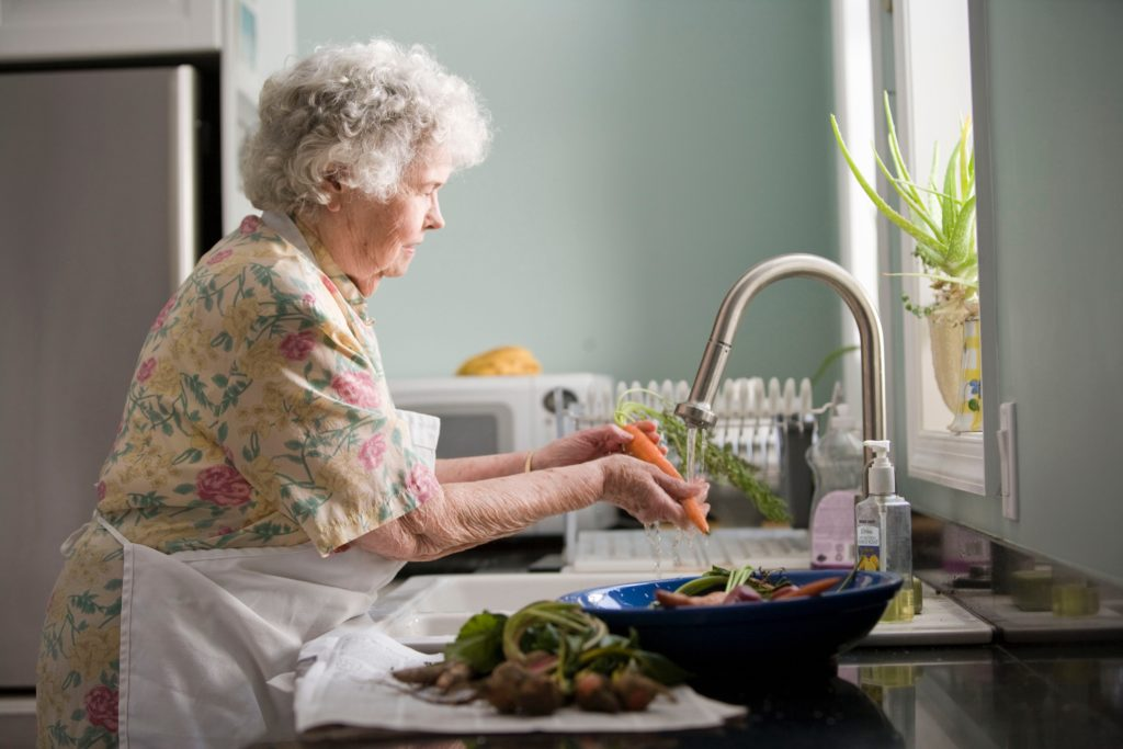 A socially isolated senior during COVID-19 pandemic washing vegetables at her kitchen sink