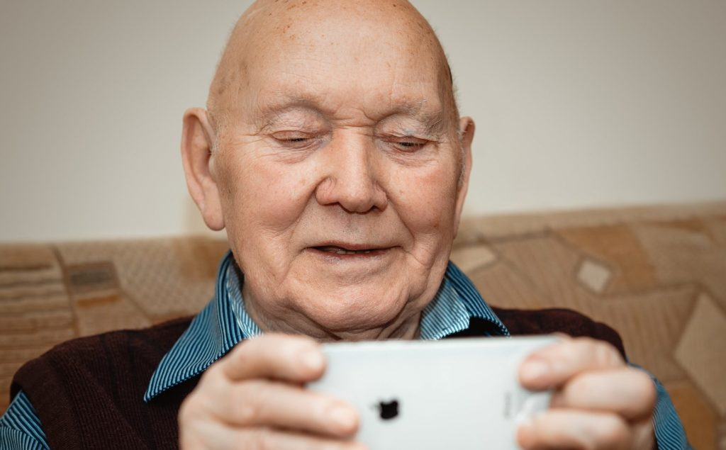 Socially isolated senior during COVID-19 pandemic using his phone for a video call with family