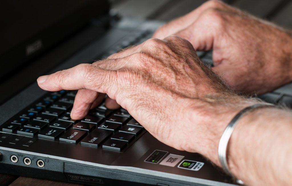 Hands of a socially isolated senior during COVID-19 pandemic typing an email to family on a laptop