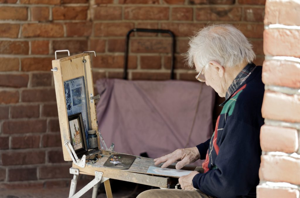 Socially isolated senior during COVID-19 pandemic painting on an easel to pass the time