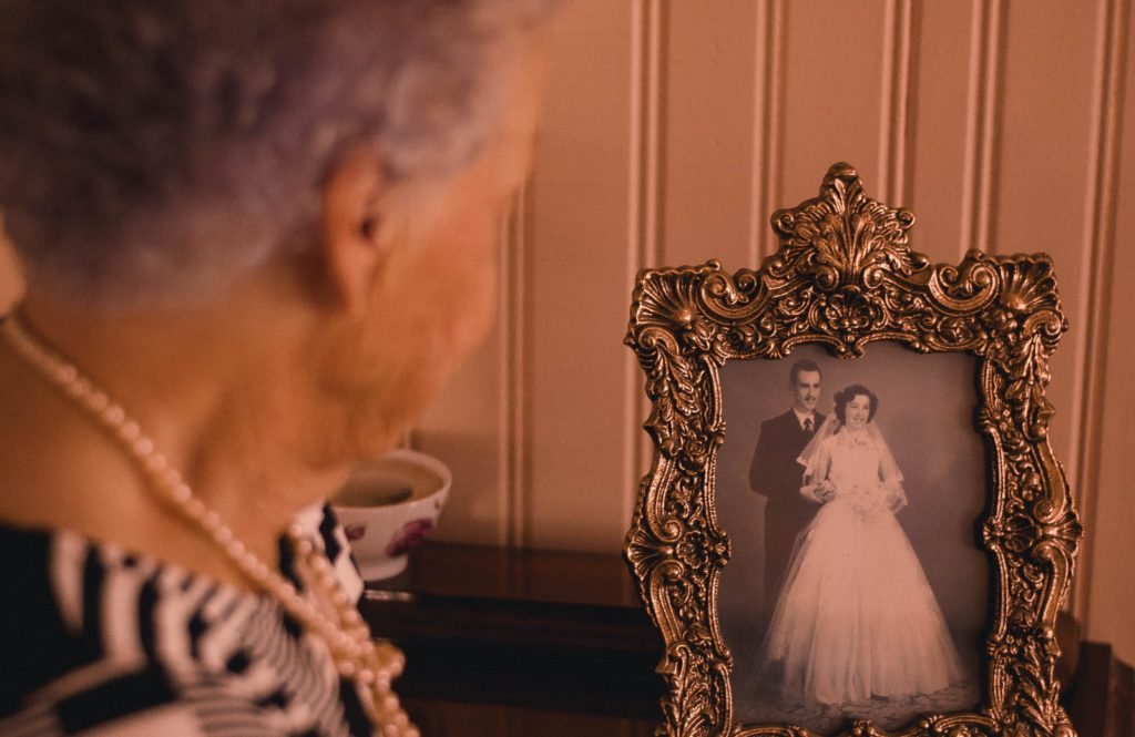 Socially isolated senior during COVID-19 pandemic reminiscing by looking at her wedding photo