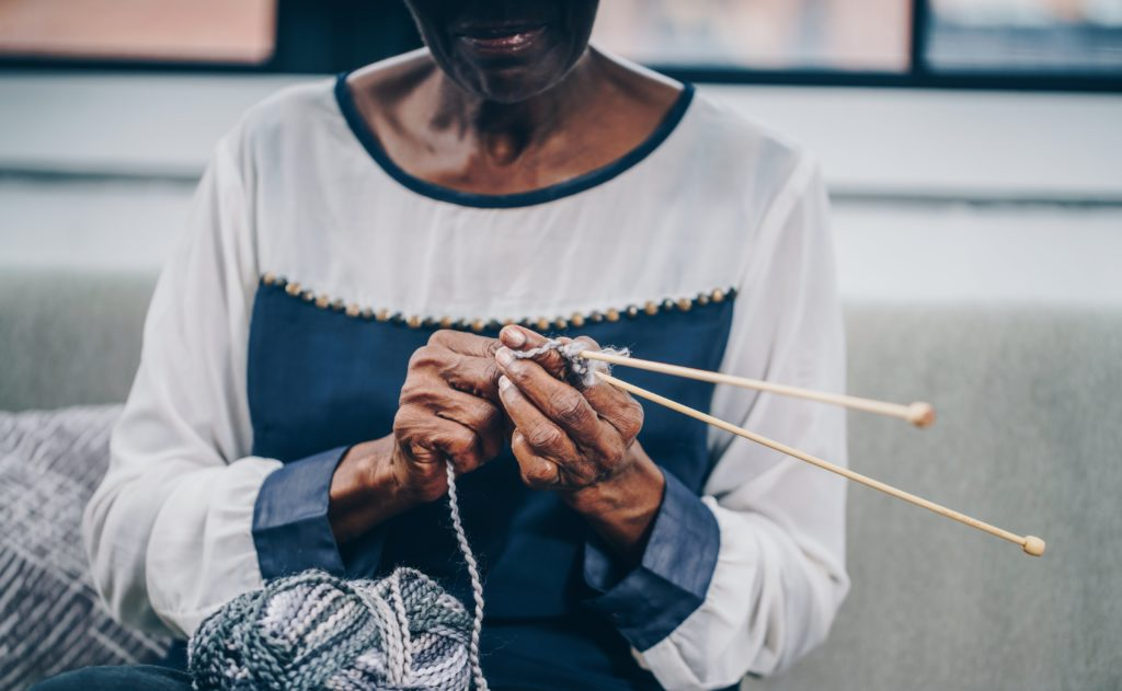 A socially isolated senior during COVID-19 pandemic knitting